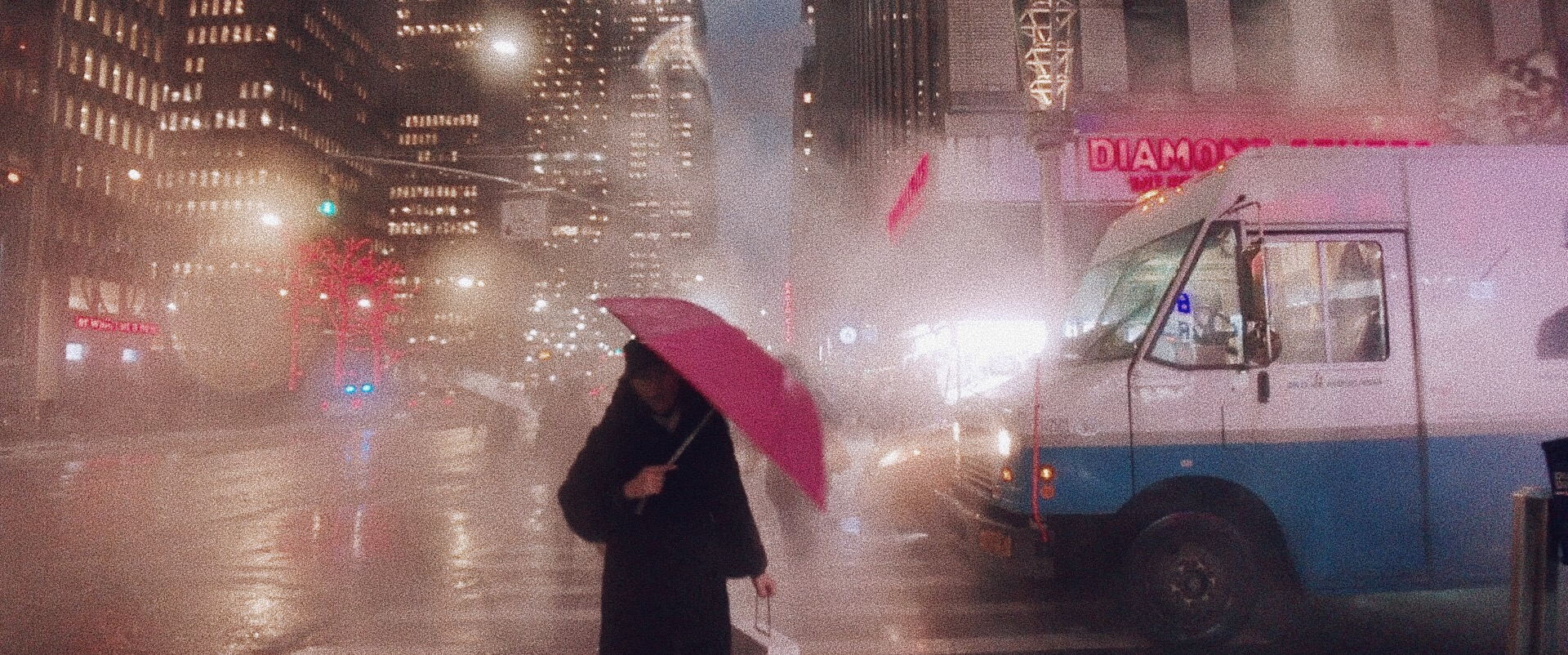 A person carries a pink umbrella through the rain and fog in the city.