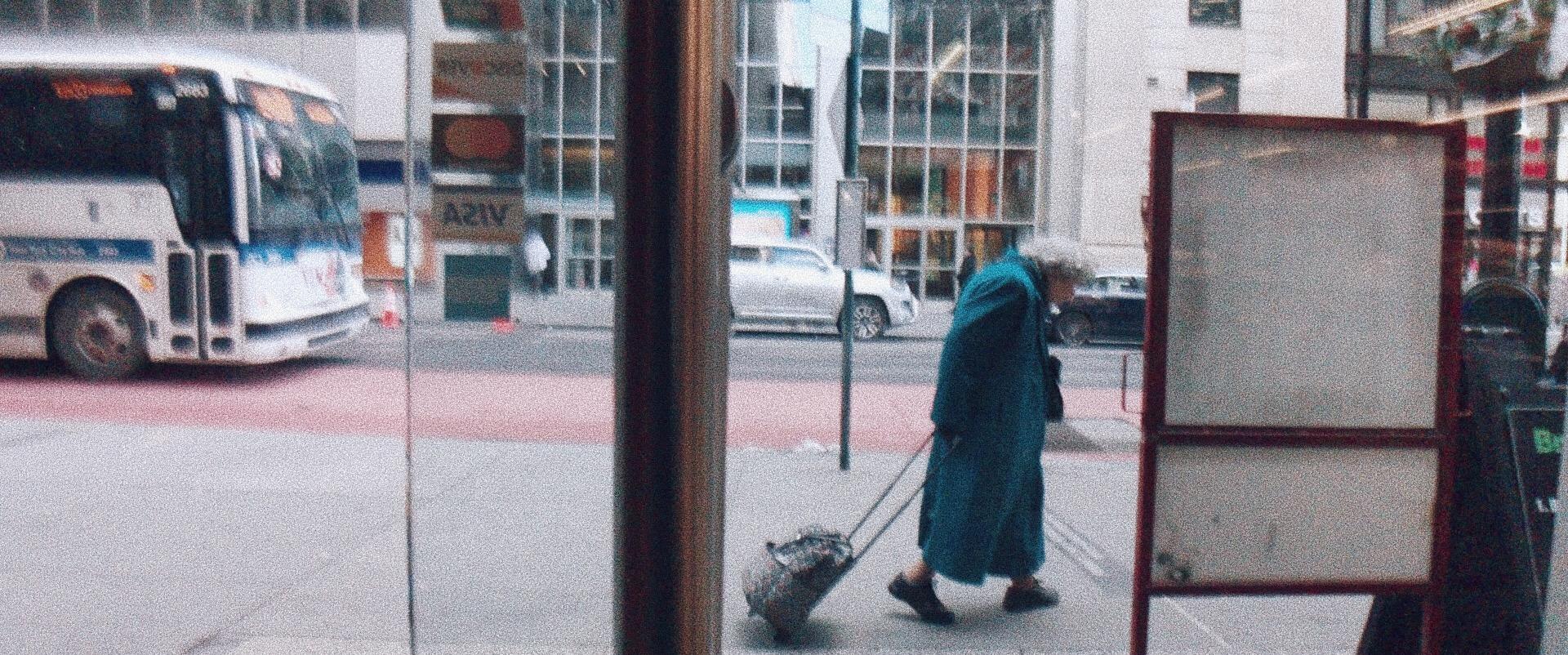 An elderly woman pulling a suitcase through downtown Manhattan.