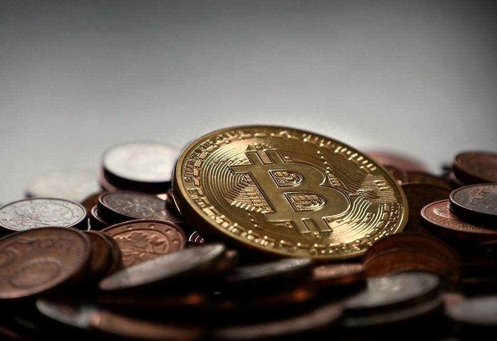 Imagem com moeda Bitcoin em destaque sobre outras moedas