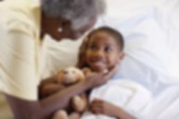 boy in bed with teddy bear with grandma tuckig him in