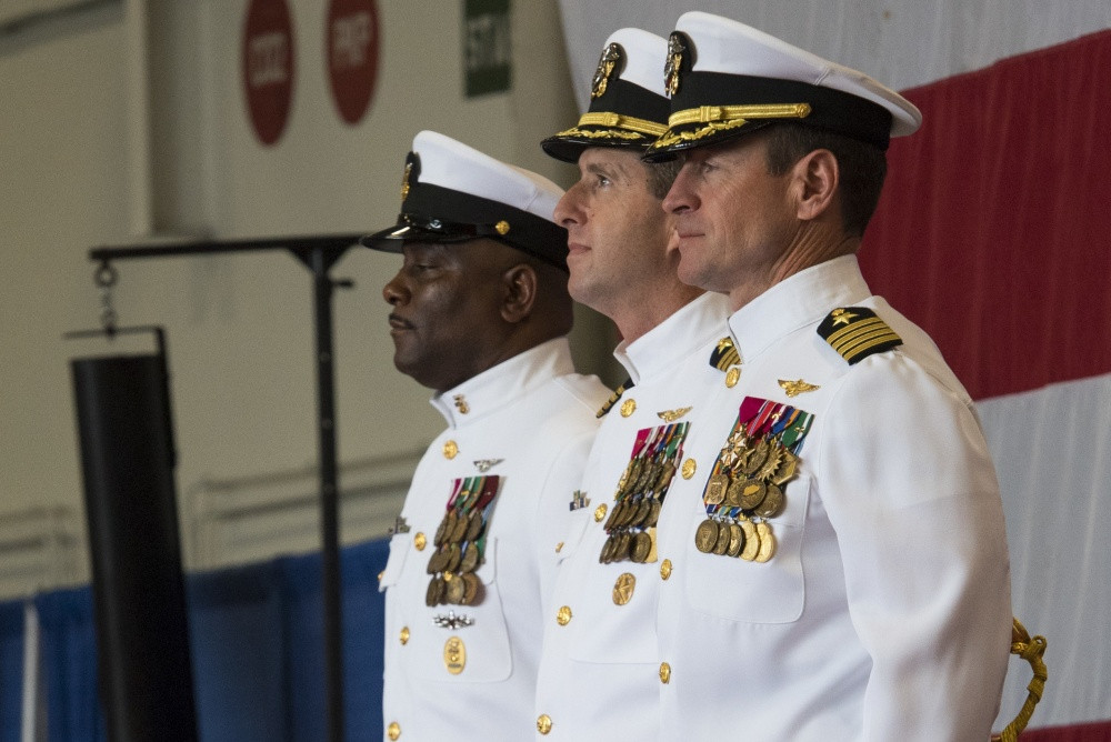 (From the left) Command Master Chief USS Harry S. Truman (CVN 75), Command Master Chief Antonio Perryman; incoming commanding officer, USS Harry S. Truman, Capt. Nicolas Dienna and off-going Commanding Officer, USS Harry S. Truman, Capt. Ryan B. Scholl (of Beltsville) stand at attention while sailors parade the colors during the Truman change of command ceremony in the ship's hangar bay. Truman hosted a change of command on the 19th anniversary week of the ship's commissioning. (U.S. Navy photo by Mass Communication Specialist Seaman Kaysee Lohmann/Released)