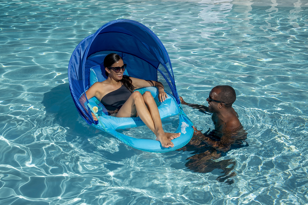 Two people in a pool. One on a float and one in the water