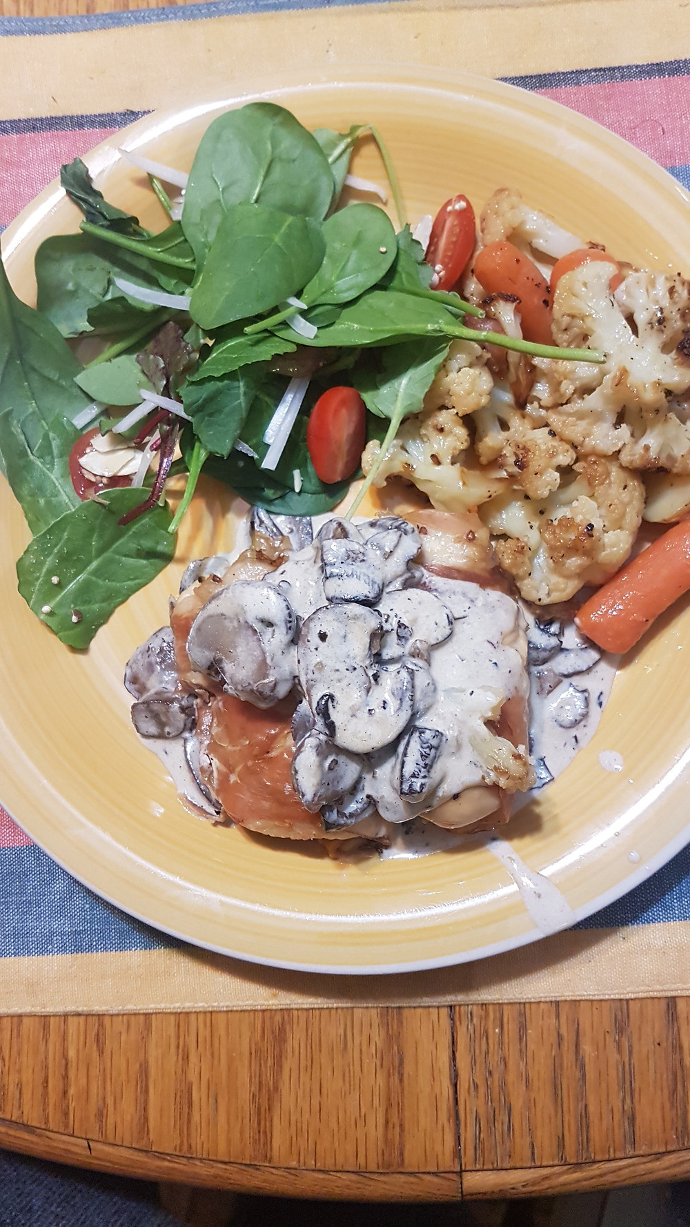Prosciutto wrapped chicken breasts, in a mushroom cream sauce, with roasted vegetables and a side salad.