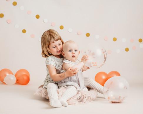 Søskenbilde av to søstre. Lillesøster sitter på fanget til storesøster. De leker med ballonger. Bilde tatt av Tina Brikland Borsheim, Studio Brikland