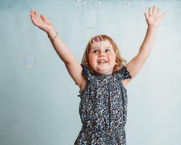 Portrett av jente i sommerkjole som strekker seg etter bobler. Bilde tatt av Tina Brikland Borsheim, Studio Brikland