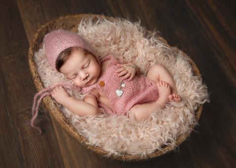 Nyfødt sovende jente i rosa strikketøy. Bilde tatt av Tina Brikland Borsheim, Studio Brikland