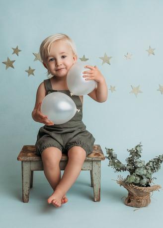 Ett år gammel gutt med ballonger. Han sitter på en grønn gammel krakk med en eucaluptus plante ved siden av seg. Bilde tatt av Tina Brikland Borsheim, Studio Brikland