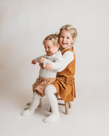 Portrett av to jenter. Storesøster har lillesøster på fanget og de smiler og ler. Bilde tatt av Tina Brikland Borsheim, Studio Brikland