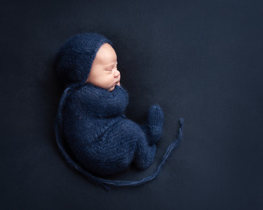 Nyfødt gutt i blå dress og lue. Bilde tatt av Tina Brikland Borsheim, Studio Brikland