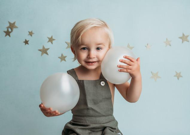 Portrett av ett år gammel gutt i grønn selershorts og med hvite ballonger. Bilde tatt av Tina Brikland Borsheim, Studio Brikland
