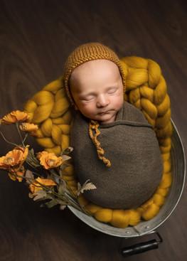 Nyfødt sovende gutt svøpt i mørkegrønnt sjal med sennpsgul lue. Sennepsgule blomster. Bilde tatt av Tina Brikland Borsheim, Studio Brikland