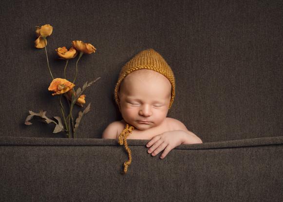 Nyfødt sovende gutt med guloransje blomster og lue. Bilde tatt av Tina Brikland Borsheim, Studio Brikland