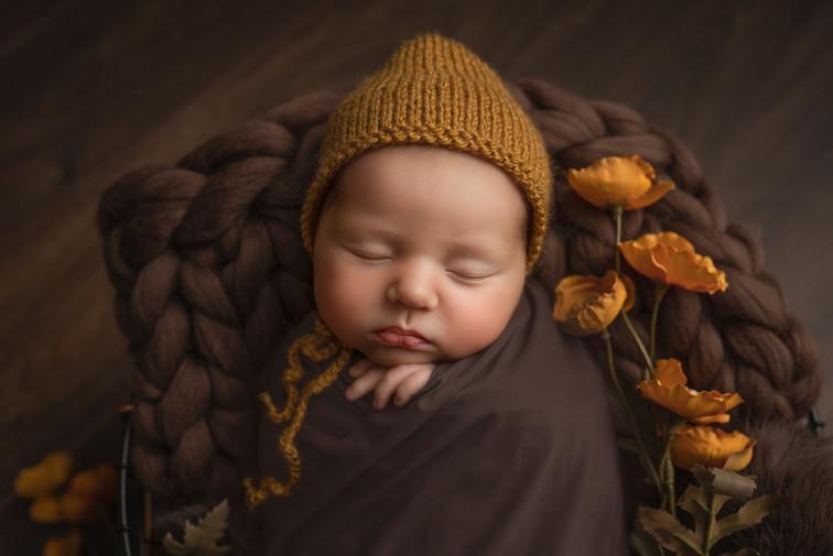 Sovende nyfødt baby med strikket lue. Nydelige høstfarger, brun pels og oransje blomster. Luen er samme farge som blomstene. Fotografert i studio av fotograf Tina Brikland Borsheim