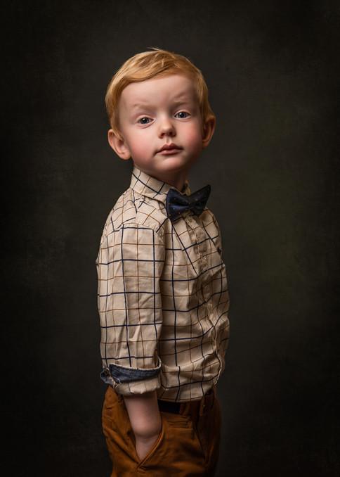 Portrett av en tre år gammel gutt med penskjorte og sløyfe. Han ser inn i kameraet med et veldig veslevoksent uttrykk mens han holder hendene i bukselommene. Han har nydelig rødlig hår og gode røde kinn. Fotografert i studio av fotograf Tina Brikland Borsheim, Studio Brikland