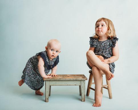 Søskenbilde av to søstre. Den minste lener seg mot en grønn krakk mens den eldste sitter på en trekrakk og lager trutmunn. Bilde tatt av Tina Brikland Borsheim, Studio Brikland