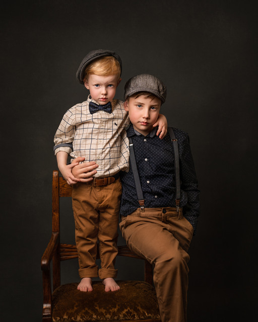 Portrett av to brødre. Lillebror står på en stol og holder armen rundt storebror. Fotografert i studio av fotograf Tina Brikland Borsheim