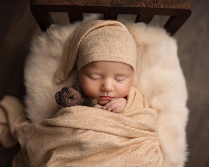 Nyfødt baby med nattlue. Ligger på mykt skinn i en liten seng, holder rundt en liten teddybjørn