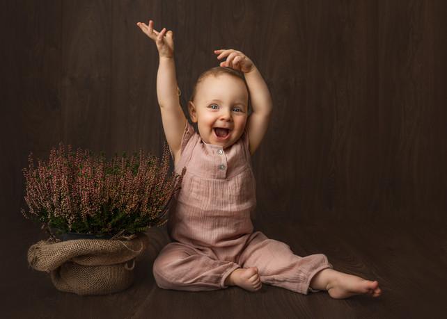 Ettårsfotografering av jente i rosa buksedrakt. Hun ler og smiler og strekker armene i været, fineart. Bilde tatt av Tina Brikland Borsheim, Studio Brikland