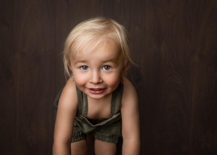 Ettårsfotografering av gutt i grønn shorts med seler. Han lener seg mot kamera og smiler, fineart. Bilde tatt av Tina Brikland Borsheim, Studio Brikland