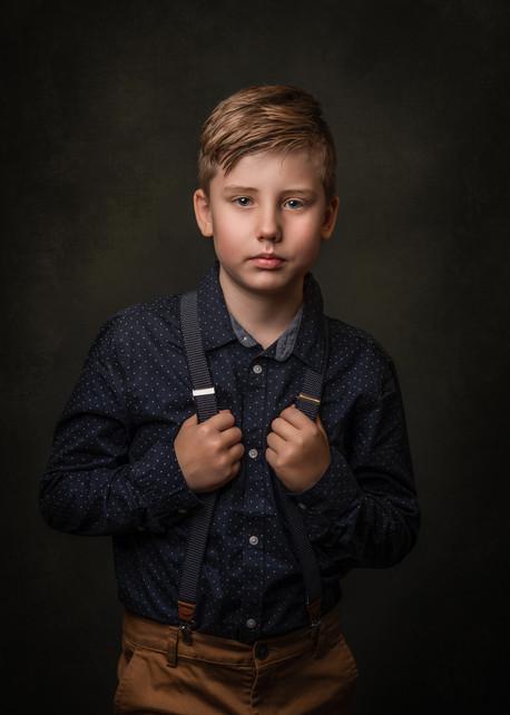 Portrett av ung gutt i mørk skjorte og bukseseler. Han ser alvorlig inn i kamera og holder rundt bukseselene oppe på brystet. Fotografert av fotograf Tina Brikland Borsheim, Studio Brikland