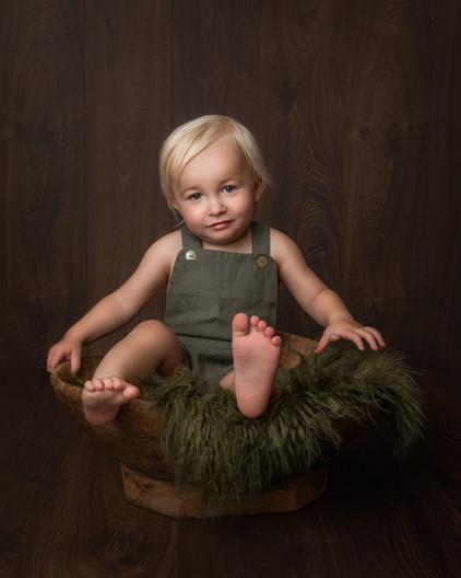 Ettårsfotografering av gutt i grønn seleshorts. Han sitter i en gammel trebolle med grønt saueskinn, fineart. Bilde tatt av Tina Brikland Borsheim, Studio Brikland