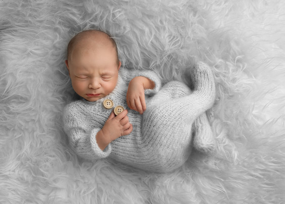 Nyfødt sovende jente, hun ligger på grå pels i en grå strikket dress. Bilde tatt av Tina Brikland Borsheim, Studio Brikland