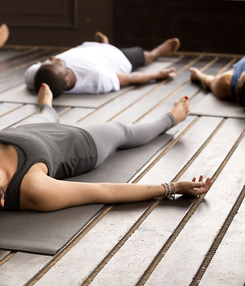 Group of young afro american and caucasian sporty people practicing yoga lesson lying in D