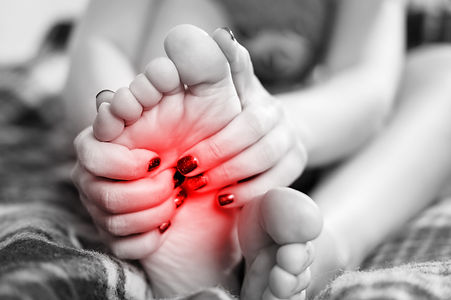 pain in the foot, girl holds her hands t