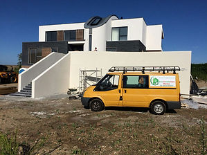 A construction site with a building with completed external render, the building has a balcony on the front with ladders going down to the floor. In the front of the building there is a yellow van with the companys logo on.