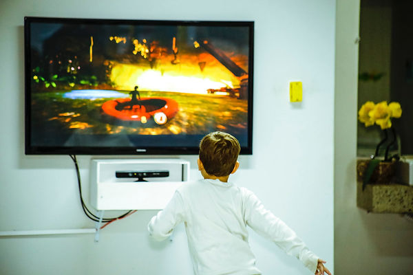 boy-standing-in-front-of-flat-screen-tv-