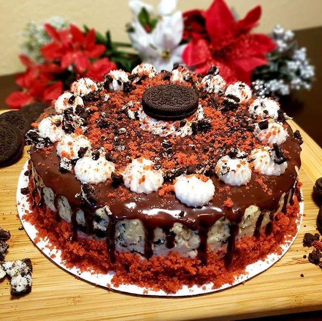 Oreo cheesecake on top of red velvet cake, topped with dark chocolate ganache, whipped cream, oreo crumbles, and red velvet crumbles