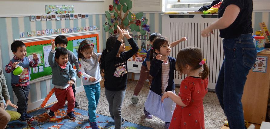 Children dancing with teacher in nursery school