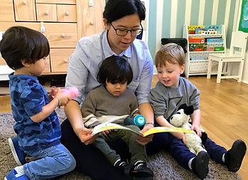 Nursery school teacher reading to children