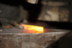 Blacksmith working metal with hammer on