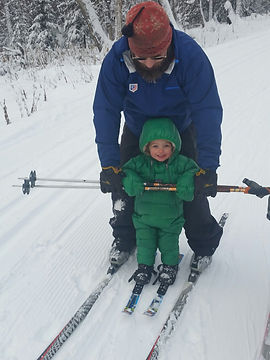 Small child skiing with parent