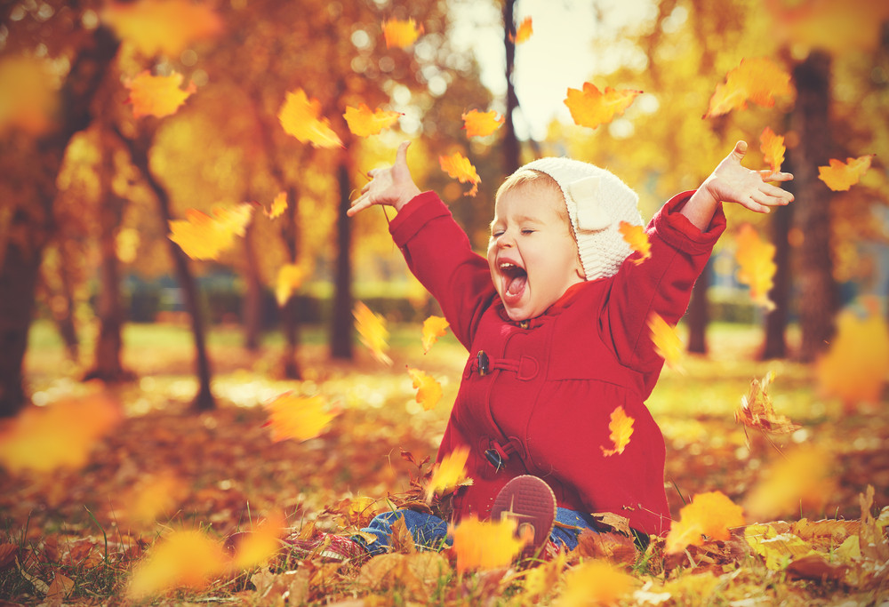 happy baby playing in leaves