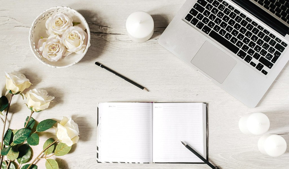 Desk with laptop computer, a notebook, flowers and candles.