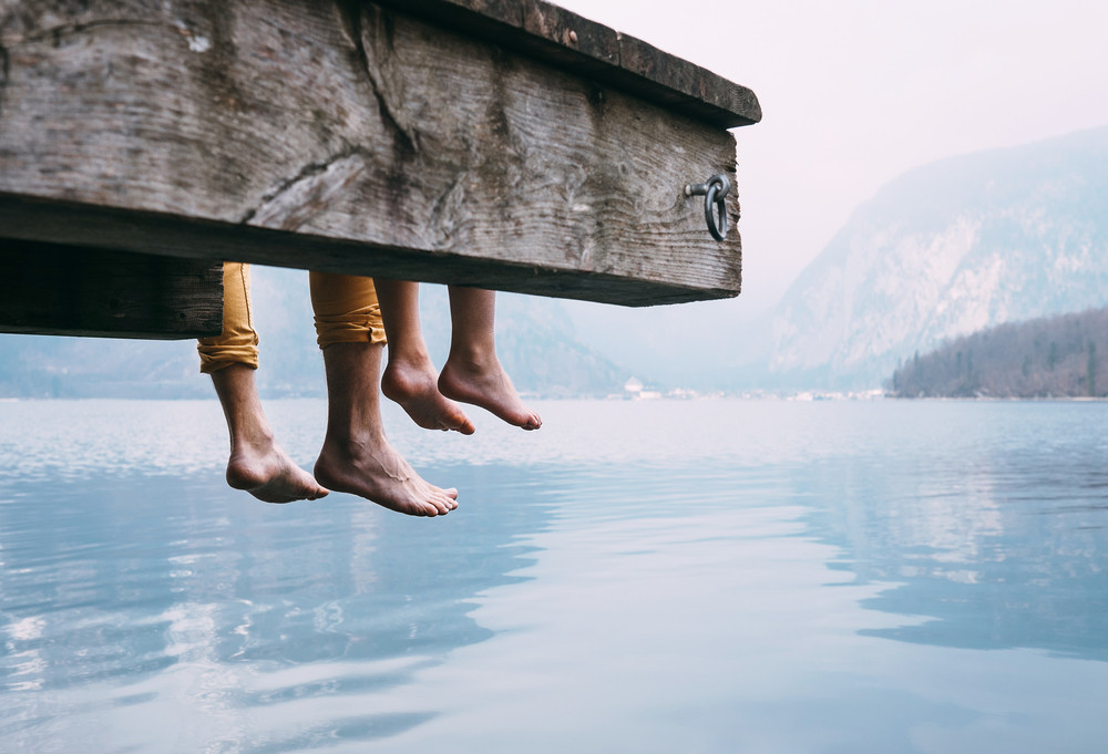 Father and son dangling their legs by a lake.