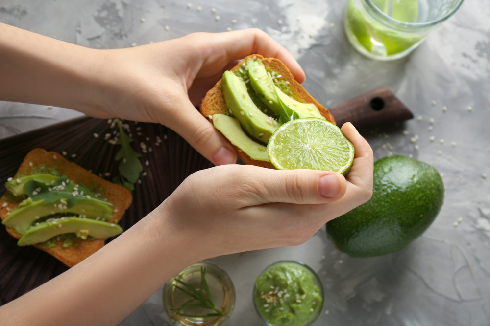 A woman holding a piece of toast with avocado and a lime