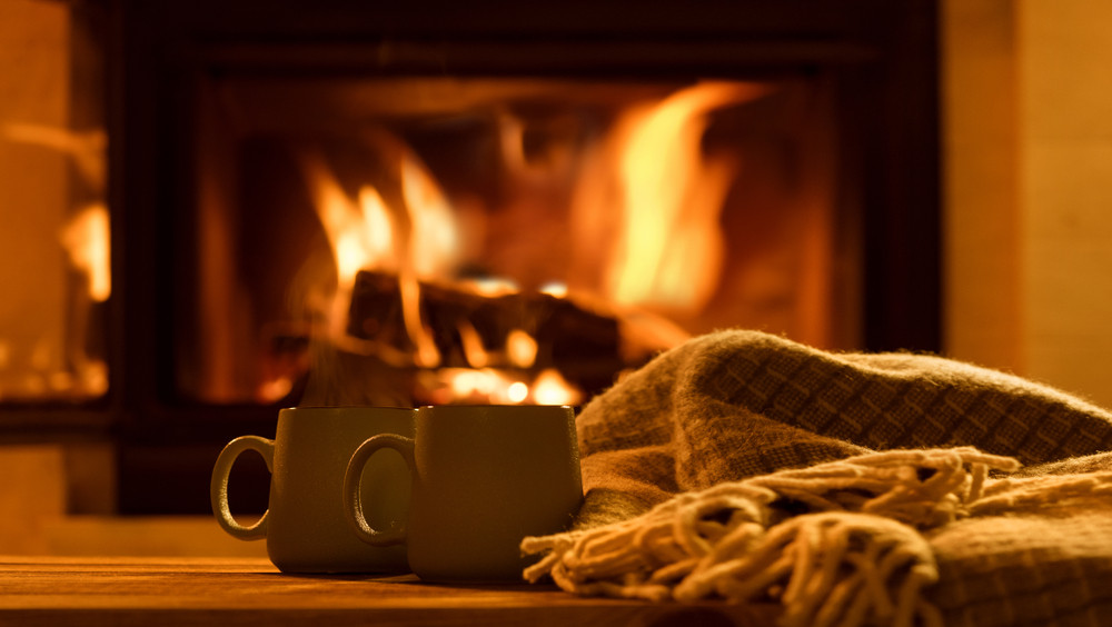 two mugs and a blanket by the fire