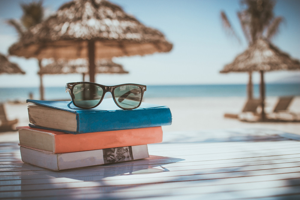 books and sunglasses by the beach