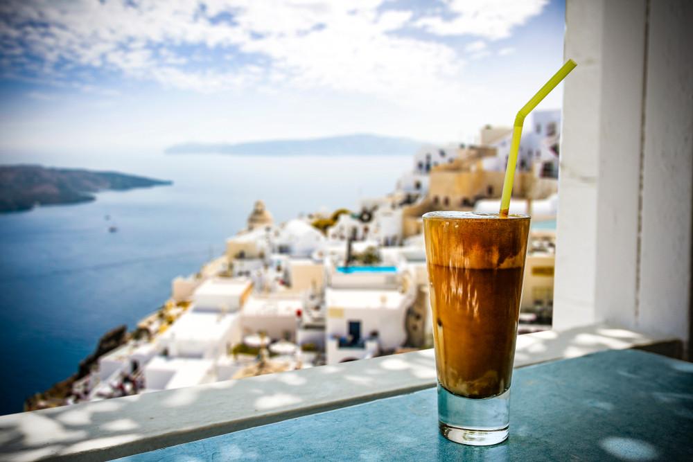 a greek frappe on a windowsill overlooking a Greek village