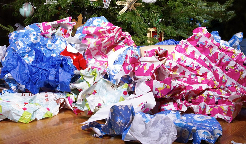 torn wrapping paper under Christmas tree