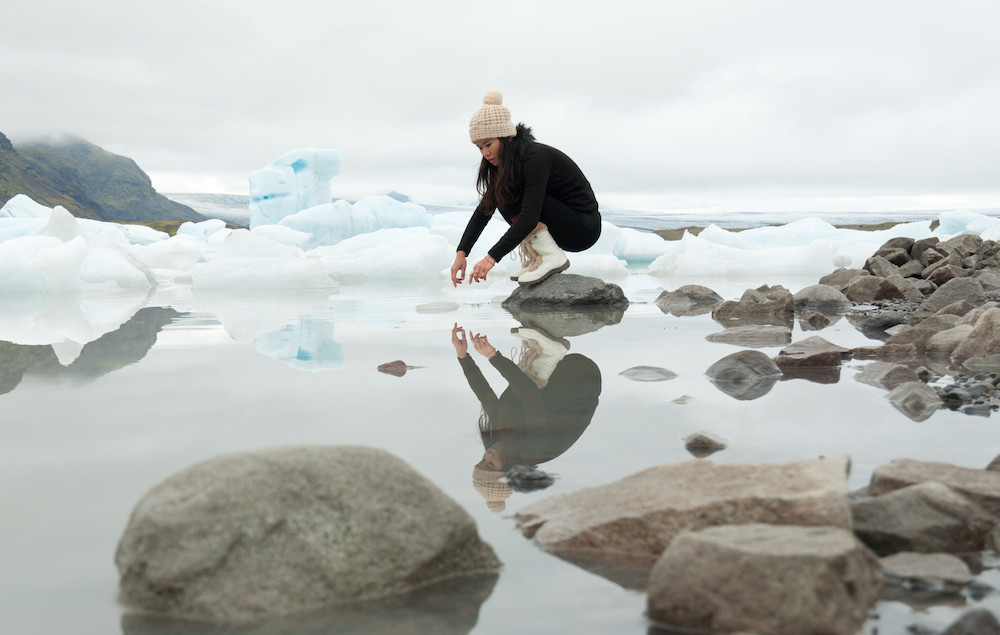 woman sitting by an iceberg