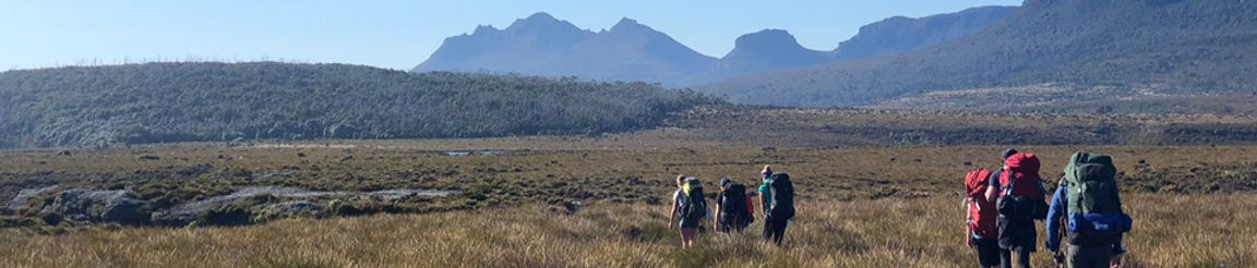 Expedition group hiking across a plain with mountains in the background