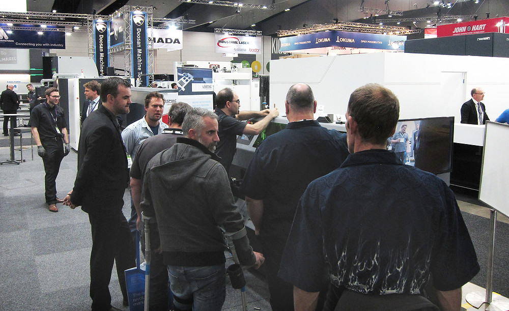 Attendees at Austech 2019 gather around the FabLight Tube & Sheet for a demo