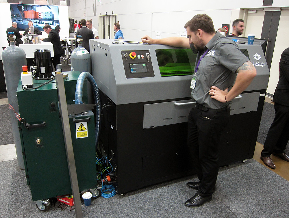 An attendee watches the FabLight Tube & Sheet cut a tube file.