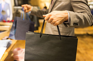 sale, fashion, retail, business style and people concept - close up of man in suit with shopping bag