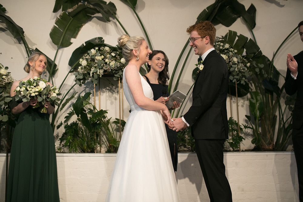 Bride and groom holding hands and laughing at ceremony