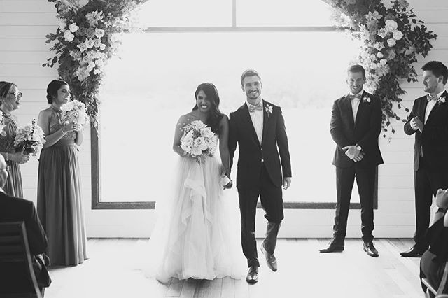 Bride and groom walking down the aisle smiling